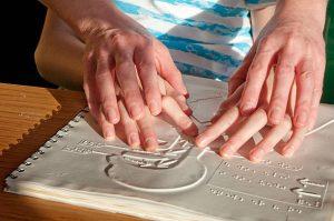 Persona mostrando la figuras en Braille a un niño