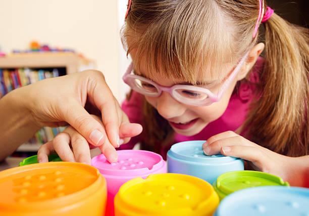 Una pequeña niña con disminución de visión jugando con con potes colores con elementos táctiles.